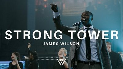 James Wilson standing singing His song Strong Tower. with other worshipers.